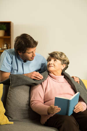 nursing assistant: Nurse caring about senior patient in nursing home