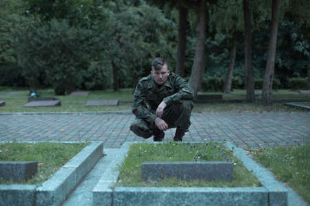 graves: Young soldier is squatting in front of comrade grave Stock Photo