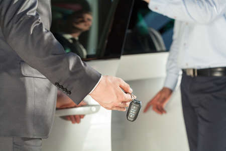 sell: Close up of car dealer giving car keys to buyer