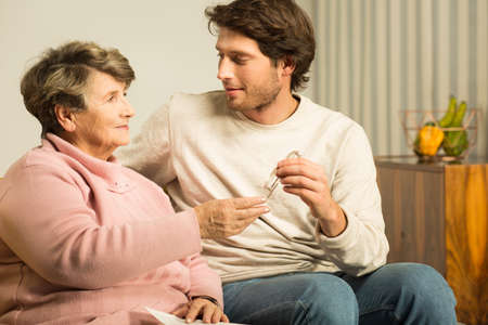 senior reading: Adult son caring about his senior mother