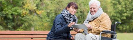 volunteers: Smiling wheelchair man is using tablet outdoor