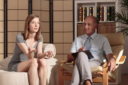 describing: Young woman is describing her problem to a therapist Stock Photo