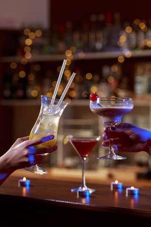 raising: Female hands raising the glass in the bar