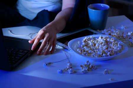botanas: Primer plano de palomitas de maíz derramado sobre la mesa y el ordenador portátil