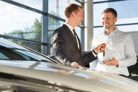 car salesperson: Photo of car dealer selling car to happy handsome buyer Stock Photo