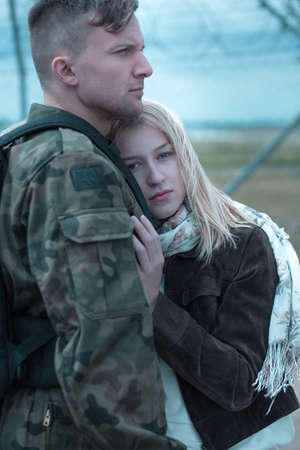 Young woman is hugging her soldier boyfriend going to army