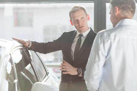 car loans: Photo of elegant salesman talking about new car model