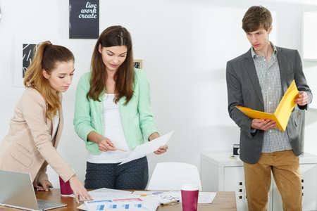 inventive: Photo of three inventive workers preparing business presentation