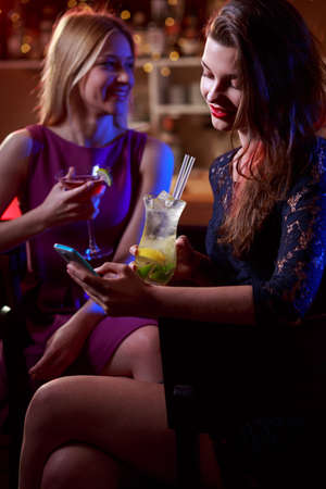 nightclub: Beauty woman drinking cocktail and sending message