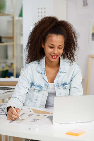 woman working: African American fashion designer drawing new project Stock Photo