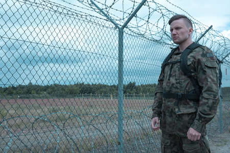 military watch: Young soldier is standing on watch in military base