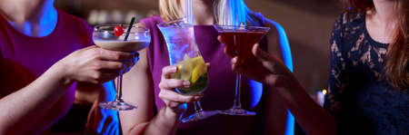 Three female friends toasting in the bar Stock Photo