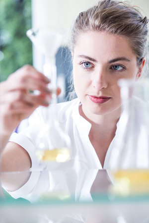 conducting: Picture of female chemist conducting test of chemical substances