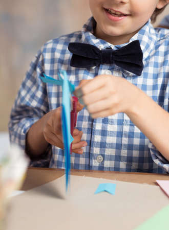 boy smiling: Close-up of toddler cutting paper in the classroom Stock Photo