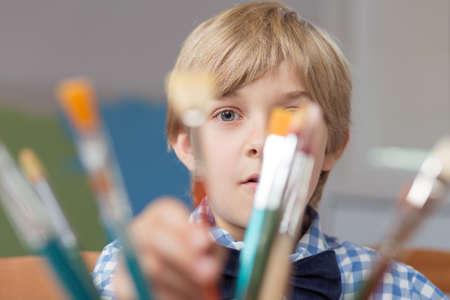 preescolar: Retrato de la pequeña artista oculta detrás de pinceles Foto de archivo