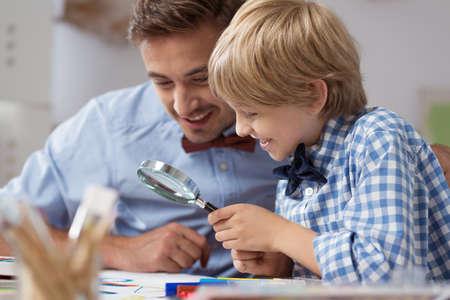 descubridor: Papá y pequeño explorador con lupa