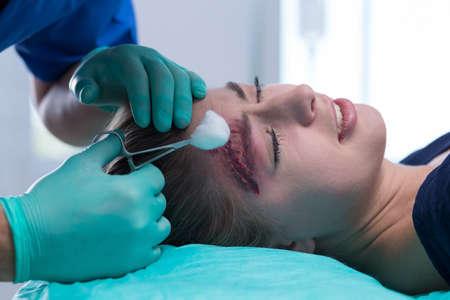 Afbeelding van arts in steriele uniform medicating hoofdwond