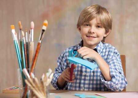 scissors: Little artist cutting paper during art class