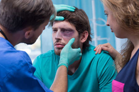 Image of doctor examining patient with black eye