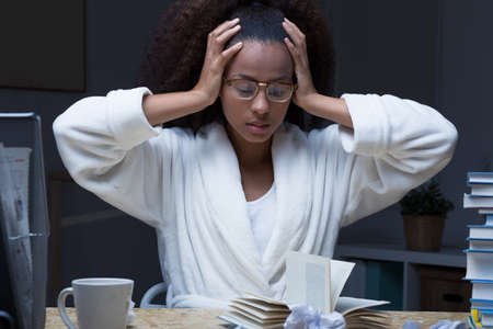 house robes: Black female student learning and panicking in the night before test Stock Photo