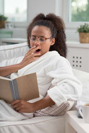 bath gown: Teenage African girl reading a boring book