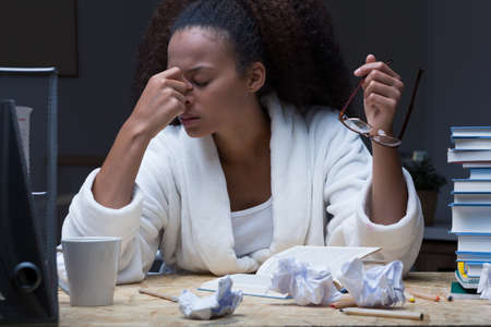 trabajando duro: Mujer joven que tiene la migra�a en la noche mientras trabajaba Foto de archivo