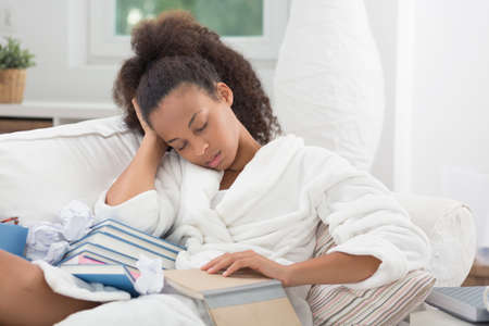 african student: Young African female student falling asleep with a book