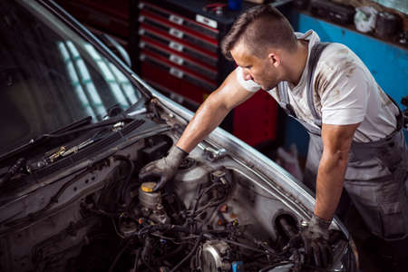 bonnet up: Mechanic is checking level of brake fluid in container Stock Photo