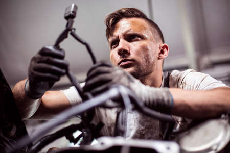 mechanist: Mechanic at service station is looking at car part Stock Photo