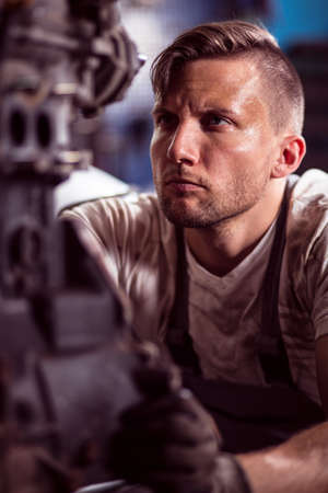 mechanist: Portrait of a mechanic at his workshop fixing motor Stock Photo