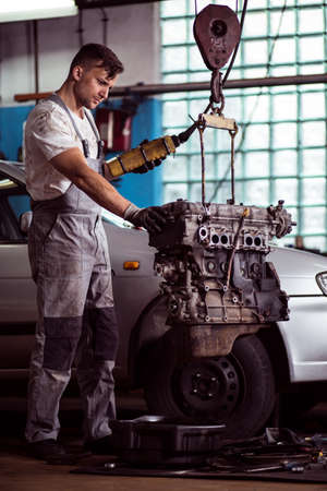 mechanist: Engine of a car is lifted by mechanic Stock Photo