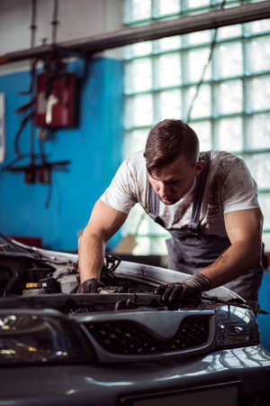 mechanist: Male technician at car service station is repairing vehicle Stock Photo
