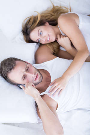 men sex: Man with mobile phone in the bed Stock Photo