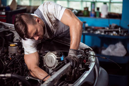 mechanist: Picture showing muscular car service worker repairing vehicle