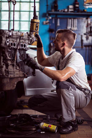 Mechanic is lifting engine for better inspection