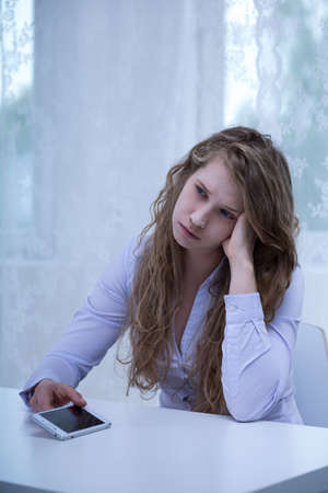 bullied: Woman is being bullied by text message Stock Photo