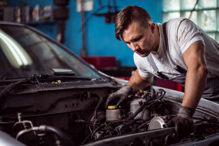 bonnet: Male mechanic is looking at parts inside car bonnet Stock Photo