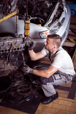 mechanist: Picture showing mechanic operating lifting device for engine Stock Photo
