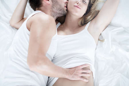 sex on bed: Man touching softly his wife during foreplay Stock Photo