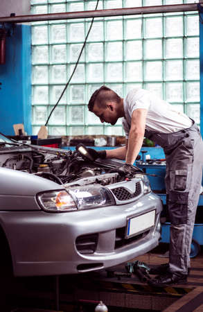 car in garage: Picture showing mechanist working at car service station Stock Photo