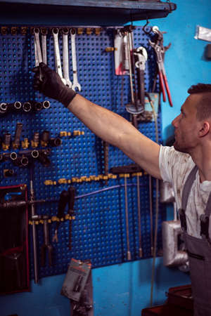 mechanist: Picture showing mechanic reaching for one of spanners Stock Photo