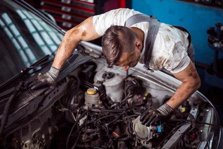 男性メカニックが車のボンネットのパーツをチェックします。