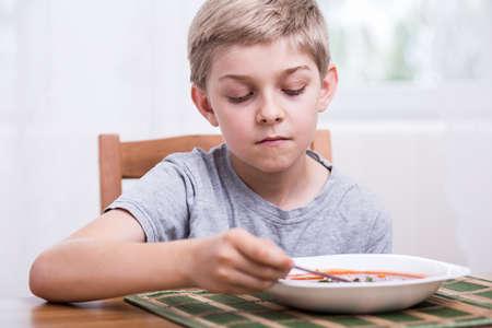 eating dinner: Sad boy eating tomato soup for dinner Stock Photo