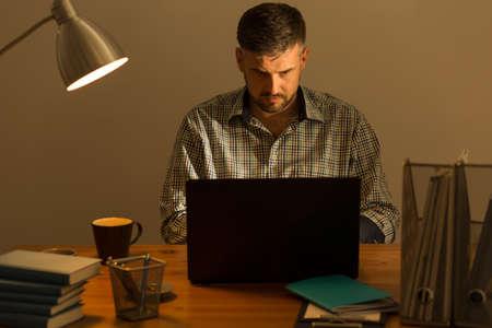 beau mec: Image of handsome guy sitting at desk working on laptop