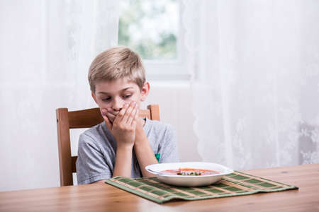 abomination: Littile boy doesnt want to eat soup Stock Photo