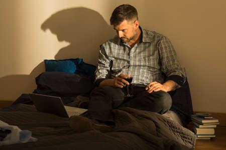 tomando vino: Retrato de hombre con el vino y el cigarrillo en la cama desordenada