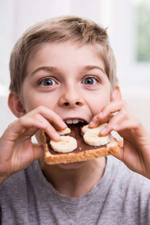 Smiling kid eating sweet sandwich with appetite