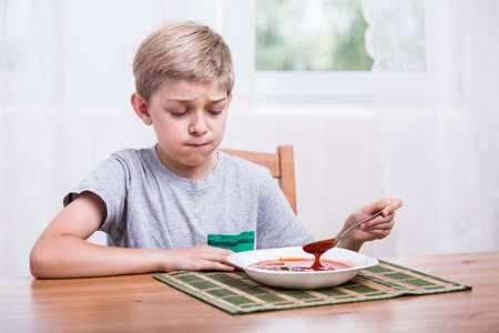 repulsive: Picky eater child eating soup with disgust Stock Photo