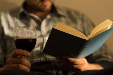 Close up of male hands holding book and glass of wine Imagens