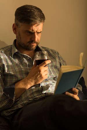 tomando vino: Imagen de hombre guapo con el libro y una copa de vino